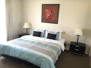 carpeted bedroom with lamps